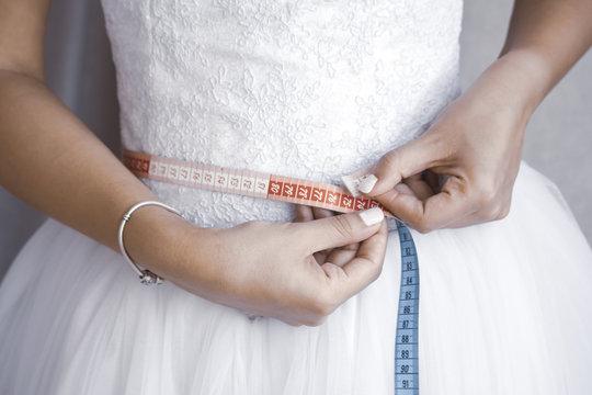 Bride measuring her waist