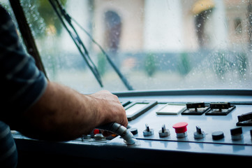 Tram driver driving an old tram car in the rain with his hand on the panel. City lights and the rain behind the glass with bokeh