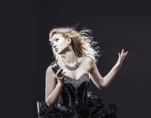 beautiful blonde woman singer in a black dress holding a microphone and sings a song.