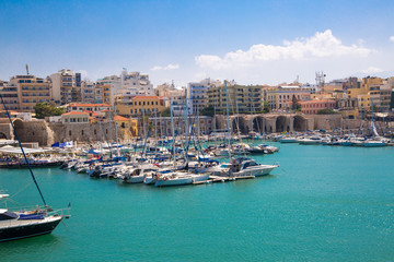 Greece, Crete, Heraklion view from the water. Old venetian harbor of Koules Fortress with fisherman boats and yacht
