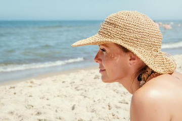 face of a woman in a hat resting by the sea in the summer