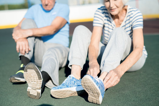 Mid section portrait of white haired senior couple tying sports shoes sitting on running track outdoors, copy space
