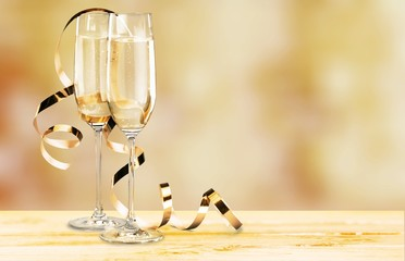 Glasses of champagne with curly ribbon on