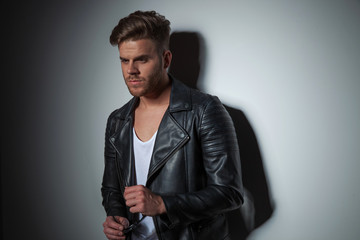 sexy man wearing leather jacket looks down to side