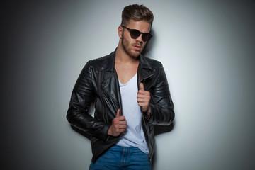 seductive man with sunglasses holding his jacket collar