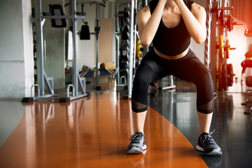 Fitness woman doing squat workout for fat burning and legs strength in fitness sports gym with sports equipment in background. Beauty and body build up concept. Sports club and Aerobic theme.