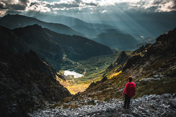 Hiking adventure photo, tourist, red backpack, beautiful evening scenery in mountains