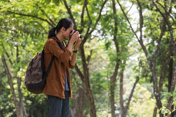 Asian male traveler carried a travel bag and take a photo by camera in the forest. concept of travel, trip