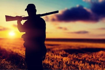 Male Hunter with Rifle on natural background Wall mural