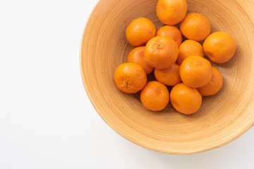 Cropped view of orange mandarines in bamboo bowl from above with copy space