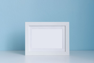 blank white picture frame on the table with blue background