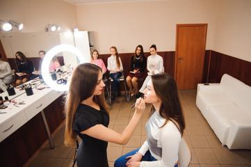 Make up artist teacher explaining l her student basic knowledge of how to apply make up properly on a brunette model girl.