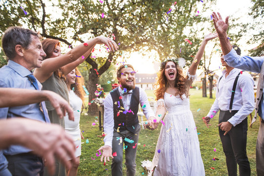 Bride, groom and guests throwing confetti at wedding reception outside.