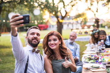 A couple taking selfie at the wedding reception outside in the backyard.