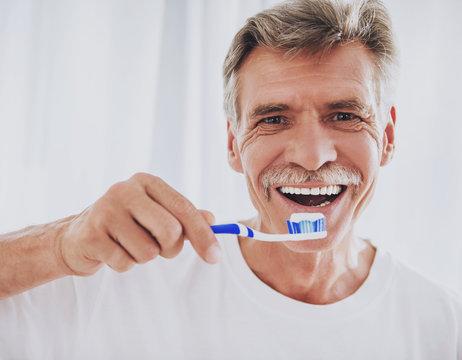 Close up. Senior Man Brushing Teeth in Bathroom.