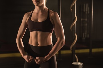 Midsection of woman showing her muscle in gym Fototapete