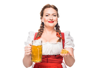 oktoberfest waitress in traditional german dress holding little pretzels and mug of light beer isolated on white background