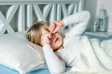 Cute little blond caucasian girl awakening at bed in morning. Child wake up early to go to school. Stretching and yawning. Healthy sleeping. Children healthcare