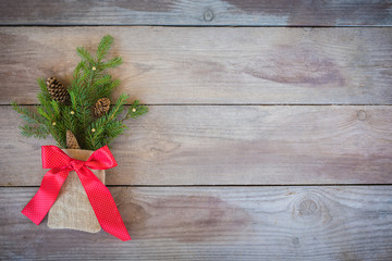 Christmas Firbranch with cones, red polka dot ribbon in the rustic bag on old wooden background