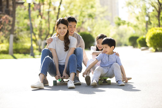 Happy young family playing with skateboards