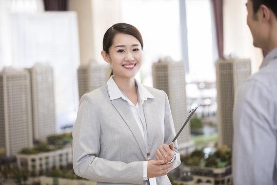 Confident realtor in sales center