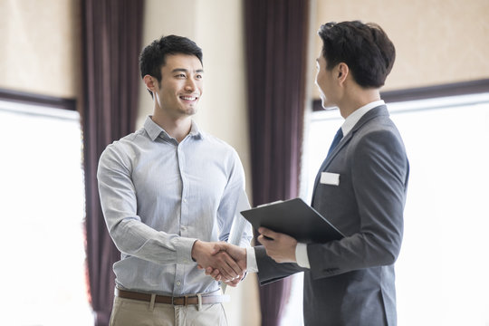 Happy young man shaking hands with realtor