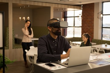 Male executive using virtual reality headset while working on