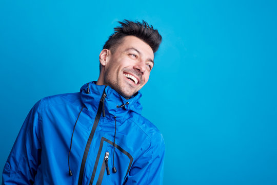 Portrait of a young laughing man in a studio with anorak on a blue background.