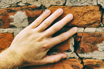 Hand on a red brick wall