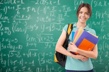 Young female student on blurred chalkboard background