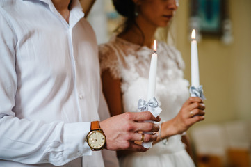 The bride, groom holds in hands wedding candle. Burn candle. Spiritual couple holding candles during wedding ceremony in christian church. close up.