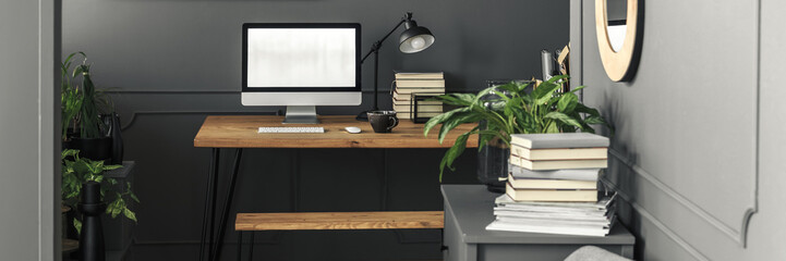Modern desktop computer, a pile of books and an industrial desk lamp on a wooden table in a stylish freelancer workspace interior with gray walls and plants
