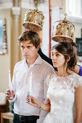The bride, groom holds a wedding candle. Burn candle. Spiritual couple holding candles during wedding ceremony in christian church. close up.