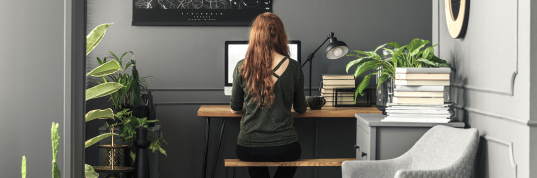 Panorama of a girl student sitting on a wooden bench by an industrial desk with a computer in a stylish bedroom interior with workspace