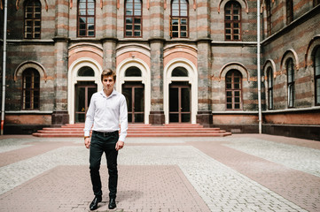 Attractive happy groom, man stand near old building outside, vintage palace outdoor.