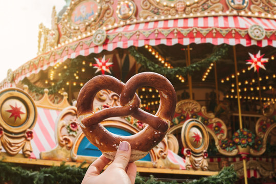 The girl is holding a traditional German pretzel. Carousel or merry-go-round and celebration in the background.