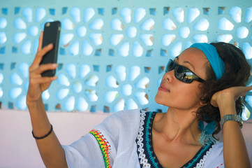 young happy and attractive Southeast Asian Indonesian girl taking selfie photo portrait with mobile phone camera posing cheerful and playful