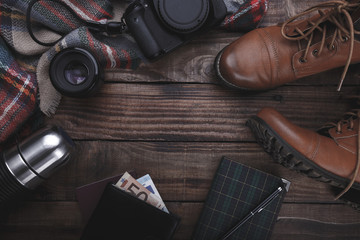 Traveler's photographer's accessories camera lense boots thermos purse with money plaid and notepad on old barn wood background
