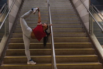 Female street dancer dancing on staircase