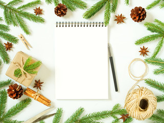 Empty white notebook and pen on white Christmas background of fir branches, cones, gifts. Letter To Santa Claus, mock up