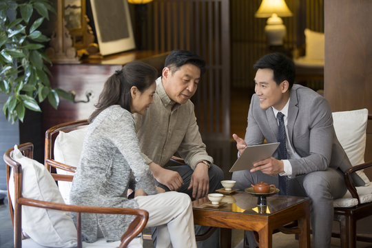 Confident financial consultant talking with mature couple