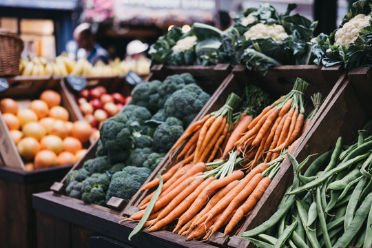 Fresh vegetables in wooden crates, on sale at a market stall.