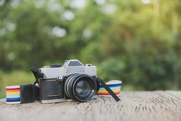 camera with green and yellow blured bokeh background outdoor on wood in morning sun light.