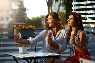 Portrait of two young women sitting together eating ice cream cones and taking selfie photo on cellphone camera in summer street cafe. Girls photographing themselves with smartphone camera.