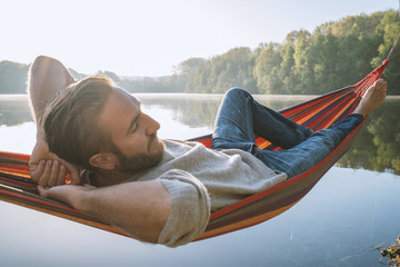 Young man by the lake hanging on hammock relaxing in the morning. People relaxation travel concept.Caucasian male enjoying nature at sunrise, shot in France, Europe