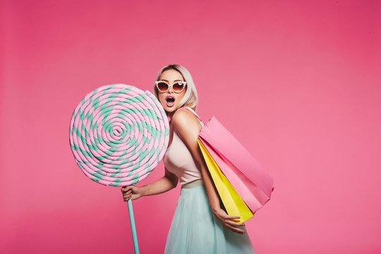 Cute model with sweets and shopping bags