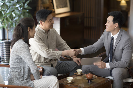 Confident financial consultant shaking hands with mature couple