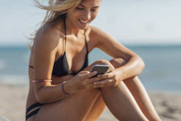 Woman Using Cell Phone on Beach