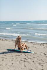 Woman Surfer Sitting on Beach
