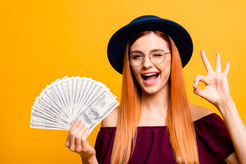 Charming and adorable young woman in hat and glasses looks at ca